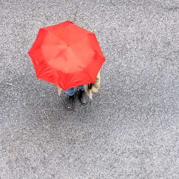 Person med oppslått rød paraply
